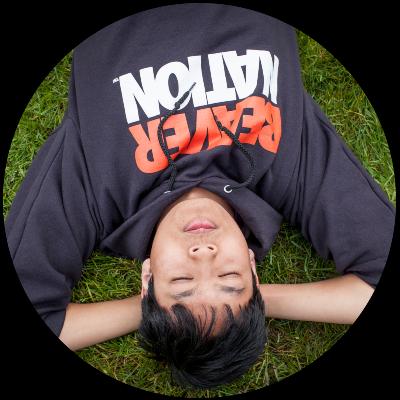 international student in Beaver sweatshirt laying on grass