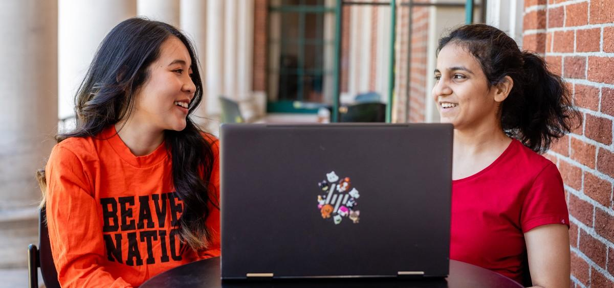 Two international students sitting together with a laptop